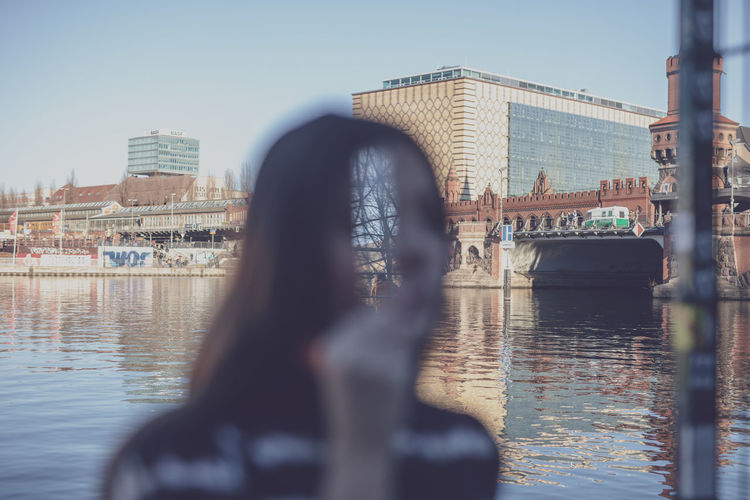 Double exposure of young woman and buildings by river in city