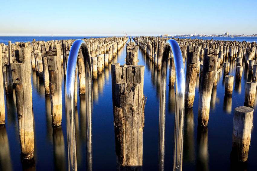 Princes Pier framed by a swimming pool hand grab rail Pier Architecture Blue Clear Sky Day In A Row Land Landscape Nature No People Outdoors Post Scenics - Nature Sea Sky Sunlight Tranquility Water Wood - Material Wooden Post