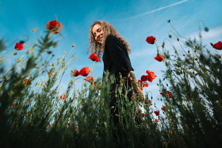 Happy smiling young woman standing on red poppy flowers in summer