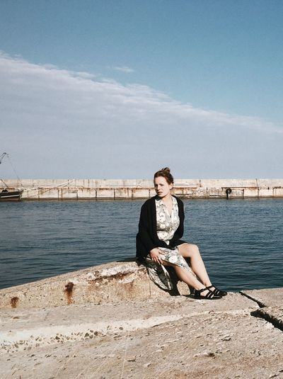 Portrait of woman sitting by harbor against sky