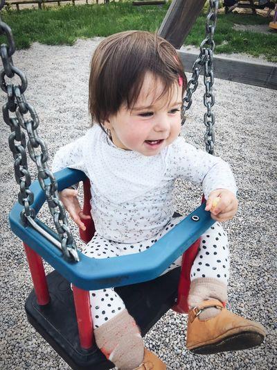Cute boy sitting on swing in park