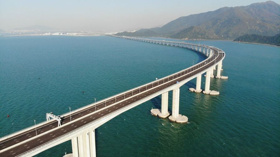 High angle view of bridge over sea against mountain