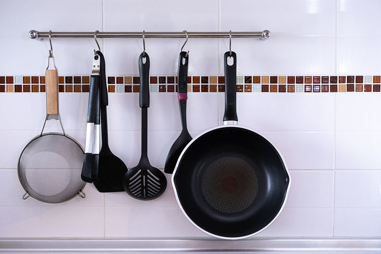 Cooking utensils hanging on rack on tiled wall