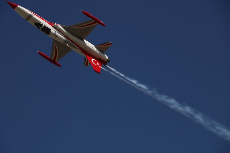 Low Angle View Of Fighter Plane Flying Against Blue Sky