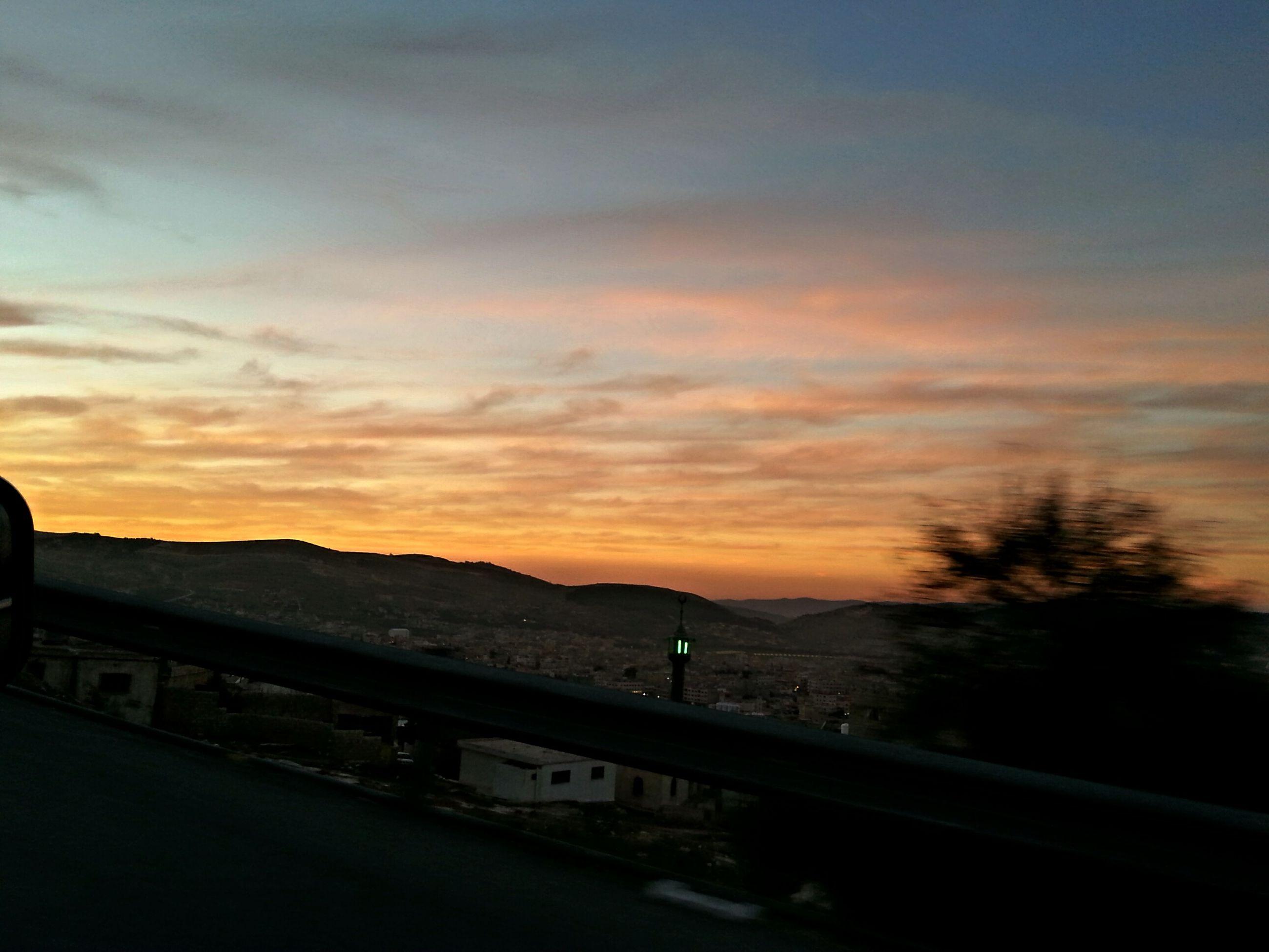 sunset, sky, orange color, silhouette, mountain, scenics, transportation, beauty in nature, cloud - sky, tranquil scene, tranquility, nature, landscape, road, cloud, railing, idyllic, dusk, dramatic sky, mountain range