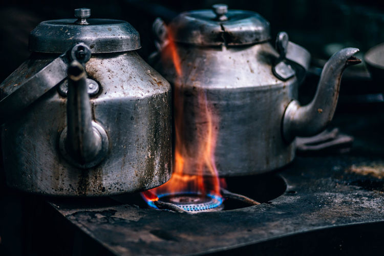 Close-up of kettles on burning stove
