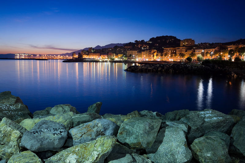 Scenic view of sea by illuminated city buildings against sky