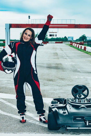 Woman Driving Go-Cart Go-carting Carting Champ Car Racing Soapbox Chart Chart Car Competitive Sport Motorsport Driver Drive Speed Sport Sport Race Motor Racing Track Activity Young Woman Driving Sports Uniform Sports Helmet Lifestyle Car Racing Fun Standing Arm Raised