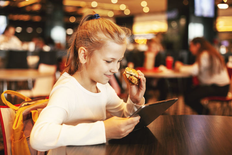 A cute schoolgirl sits in a cafe, plays on a tablet and eats a hamburger. happy child eating