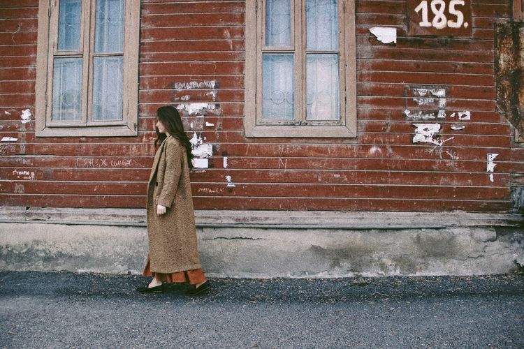 Full length of woman standing on street against building