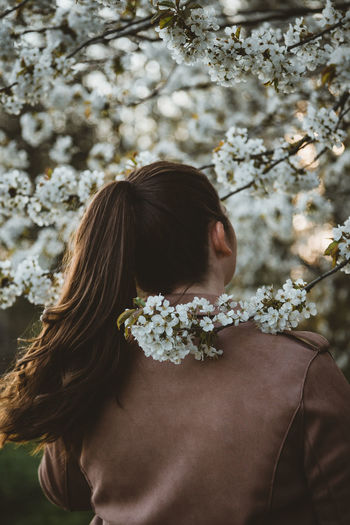 Portrait of woman with cherry blossoms outdoors