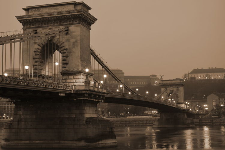 Chain Bridge Over River At Dusk