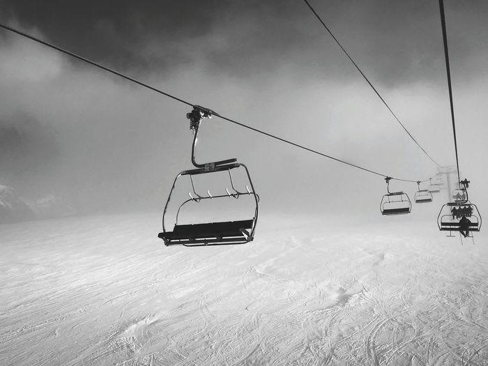 Ski Lift Over Snowy Mountain Against Sky