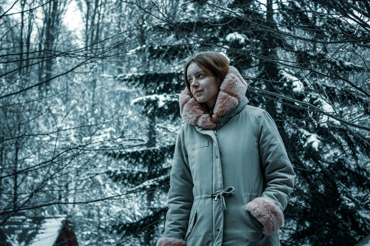 Woman standing while looking away against snow covered trees in forest