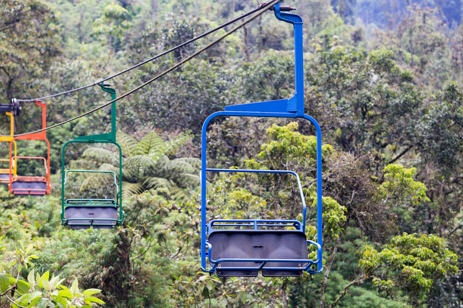 Blue, green orange and yellow chairs on the ski lift at the Recinto del Pensamiento nature reserve near Manizales, Colombia. Chair Cloud Colombia Electric Green Latin Manizales Recinto Ski Lift South America Andean Cloud Forest Coffee Triangle Colombian  Colorful Day Fog Forest Lift Mist Nature Outdoors Park Pensamiento