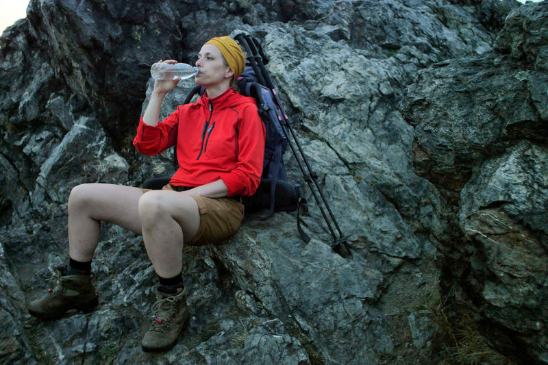 Full Length Of Woman Drinking Water While Sitting On Rock Formation