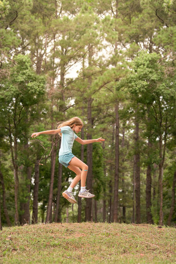 Full length of woman jumping in forest