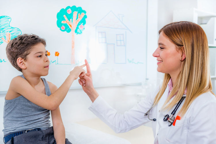 Pediatrician Doing Medical Exam with Boy Doctor  Pediatrician Medical Child Boy School Boy Measuring Arms Hands Finger Medical Exam Development Growth Hospital Clinic Patient Health Kid Care Childhood Female People Exam Professional Examination White Healthy Office Sick Adult Illness Diagnostic Lifestyle Woman Examining Occupation Pediatric Specialist Examine Diagnosis Expertise Indoors  Pediatrist Visit Lab Coat Checking Two People