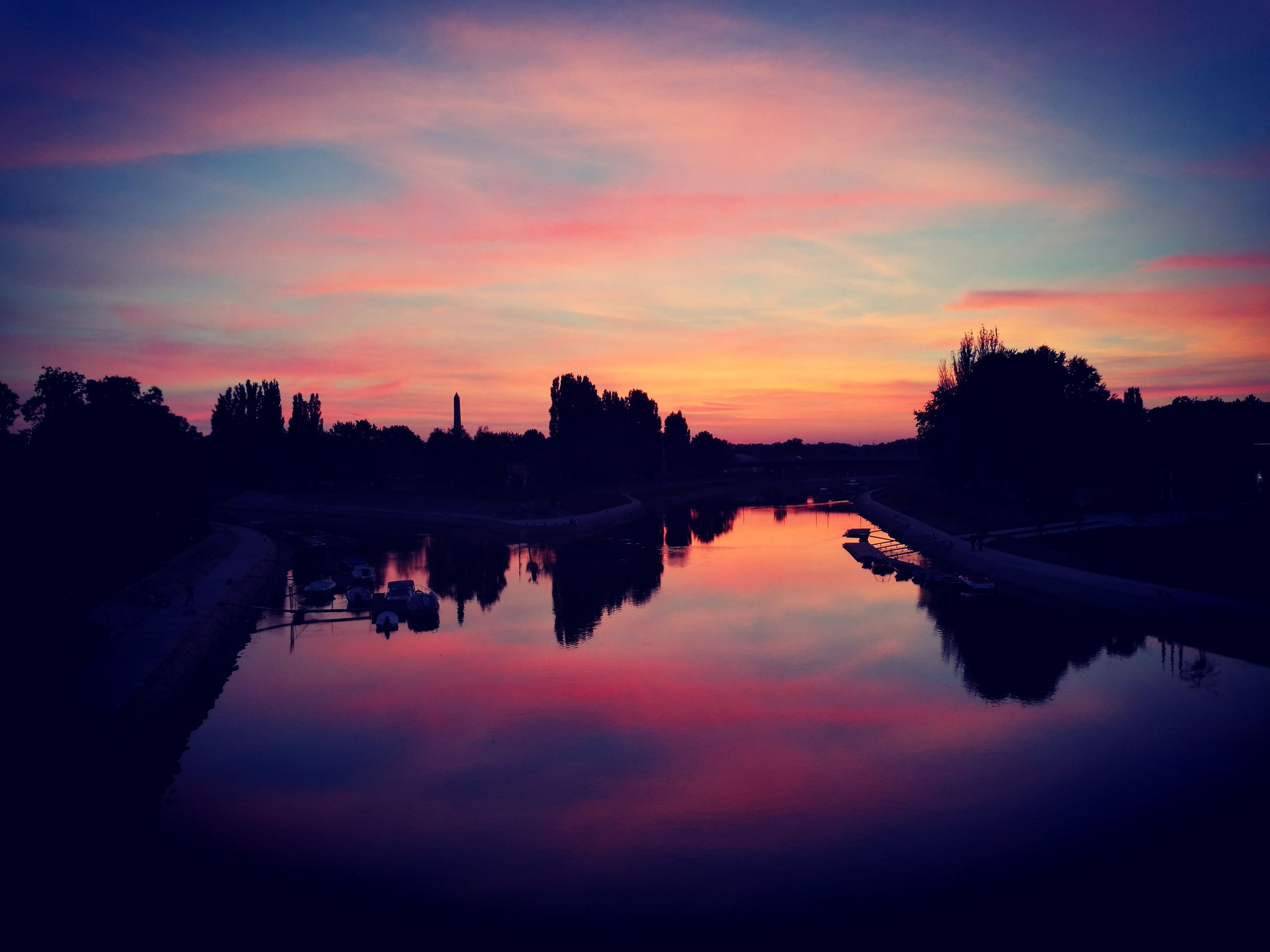 reflection, water, sunset, silhouette, scenics, lake, tranquil scene, tranquility, calm, waterfront, standing water, beauty in nature, orange color, idyllic, outline, nature, dark, sky, majestic, cloud, outdoors, blue, cloud - sky, non-urban scene, countryside, canal, moody sky, atmospheric mood, dramatic sky, no people, atmosphere