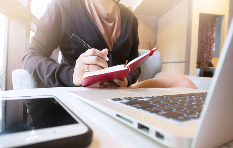 Midsection Of Businesswoman Writing In Diary While Using Laptop At Home
