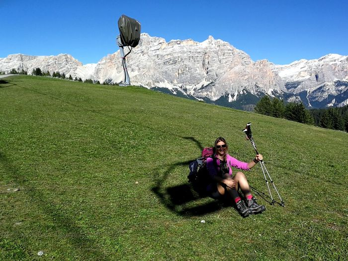 Portrait of woman holding hiking poles while sitting on field