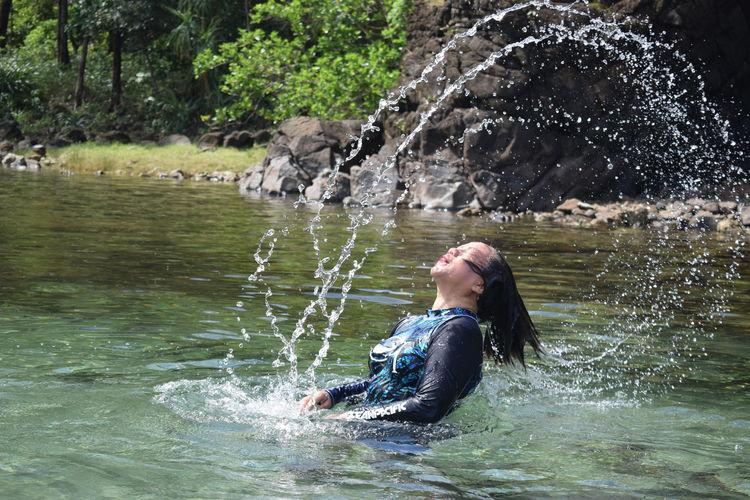 Woman Splashing Water In Lake