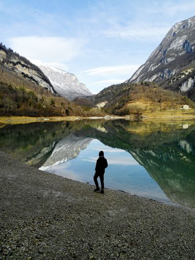 High angle view of person standing by lake against mountains