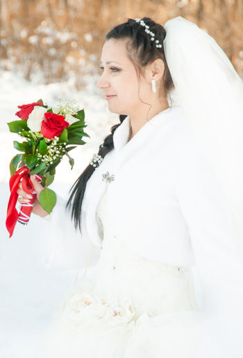 Bride Holding Flower Bouquet While Standing Outdoors