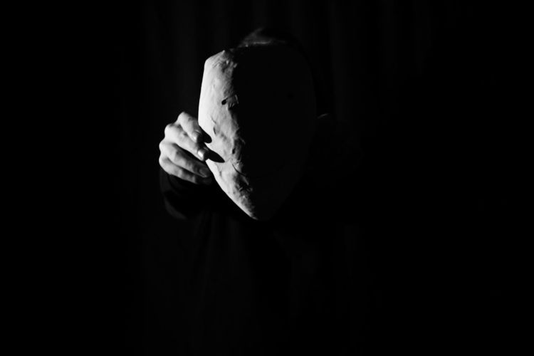 Midsection of person holding mask in darkroom