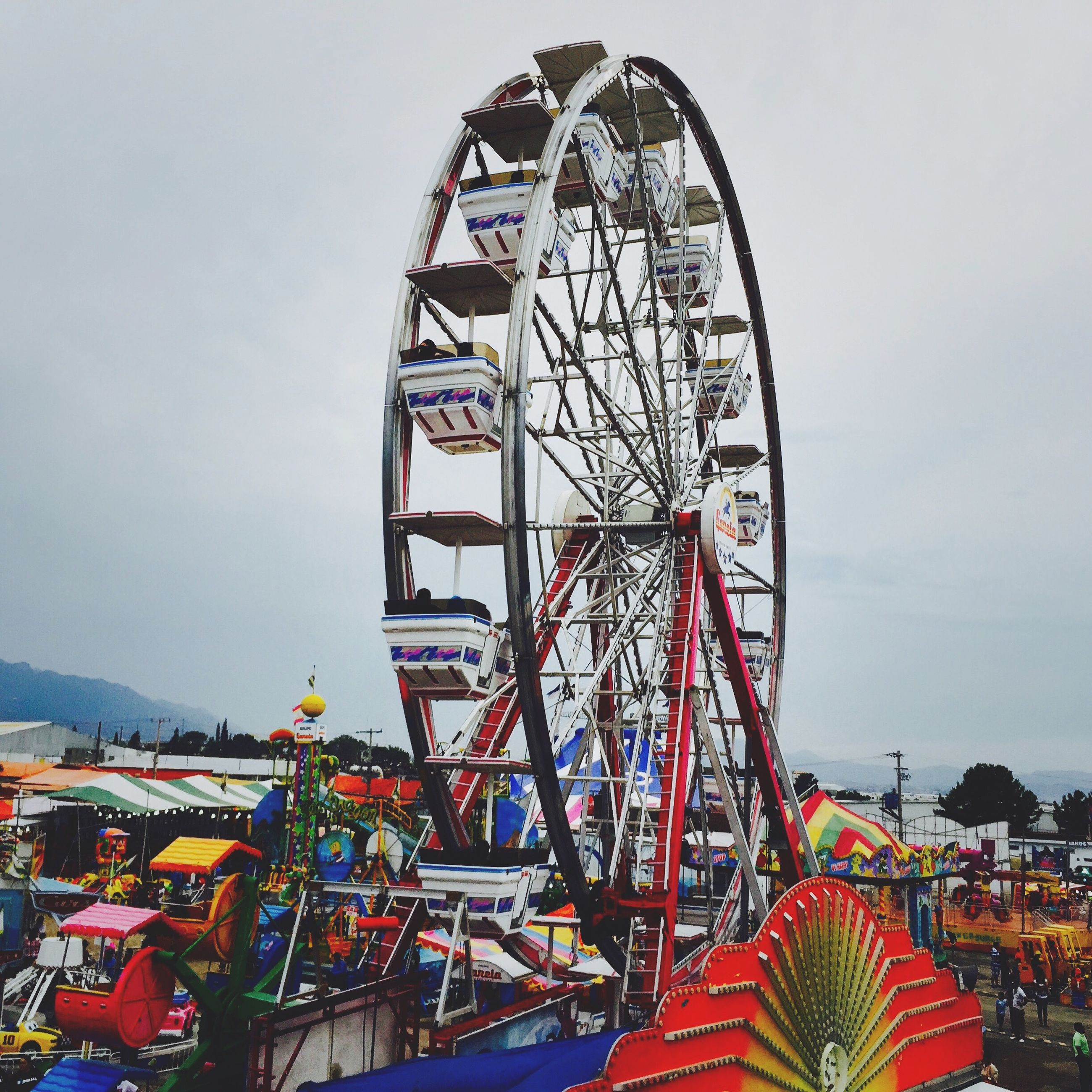 amusement park, amusement park ride, ferris wheel, arts culture and entertainment, sky, low angle view, multi colored, built structure, fun, architecture, outdoors, day, leisure activity, cloud - sky, enjoyment, clear sky, no people, transportation, traveling carnival, incidental people