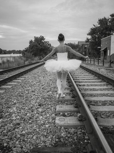 Full length rear view of ballerina walking on railroad track against sky