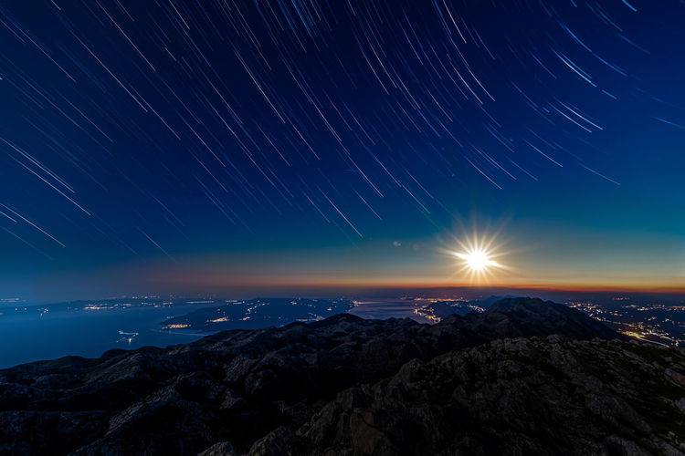 Scenic view of mountain against sky at night with sunset
