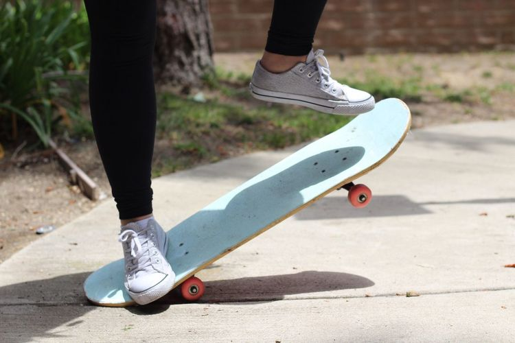 Low Section Of Woman Skateboarding At Park
