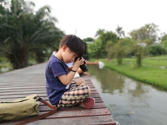 Side View Of Boy Looking Through Binoculars Sitting On Boardwalk Against Sky