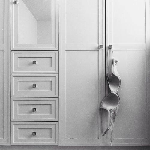 Bra hanging on door of cabinet
