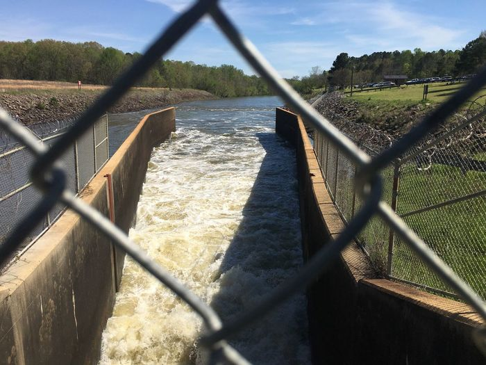 EyeEm Selects The dam is open and I had to get this shot from the fence over it Chainlink Fence Safety Protection Focus On Background Day Metal Water Outdoors Sunlight No People Sky Shadow Nature Scenics Landscape Sea Beauty In Nature