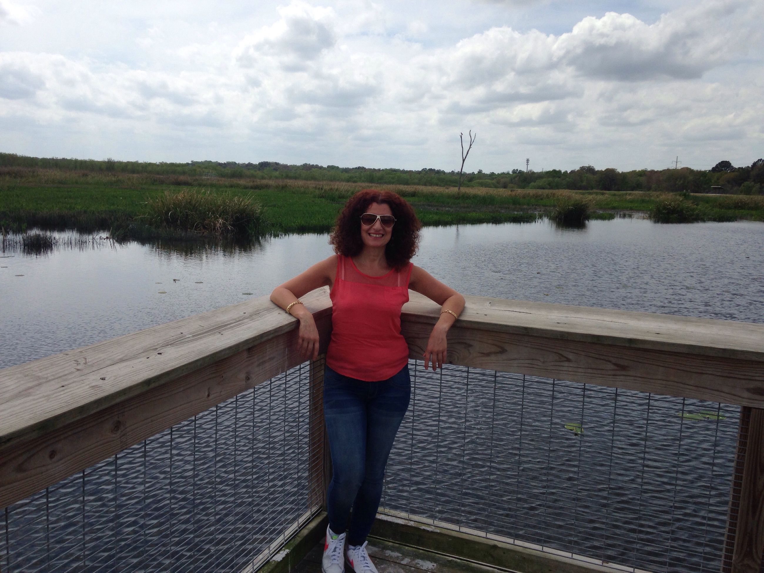 water, standing, casual clothing, person, sky, young adult, lifestyles, looking at camera, full length, portrait, leisure activity, front view, railing, lake, young women, three quarter length, smiling, cloud - sky