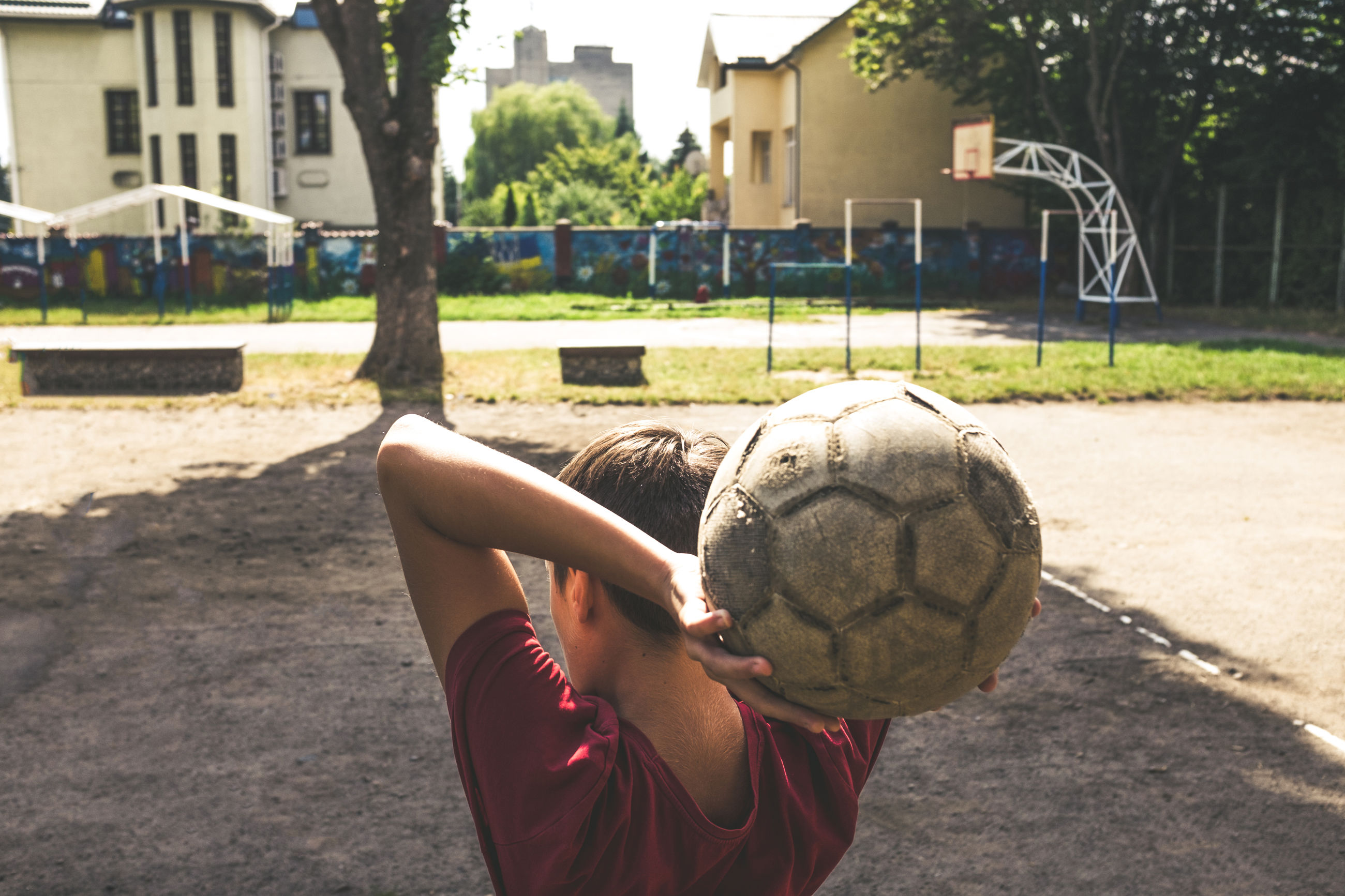 real people, soccer, one person, soccer ball, holding, sport, built structure, day, leisure activity, architecture, childhood, building exterior, human hand, ball, lifestyles, focus on foreground, playing, soccer field, outdoors, soccer player, close-up, court, basketball - sport, soccer uniform