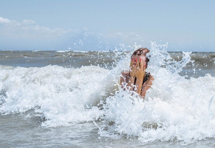 Close-up of woman covering face in sea