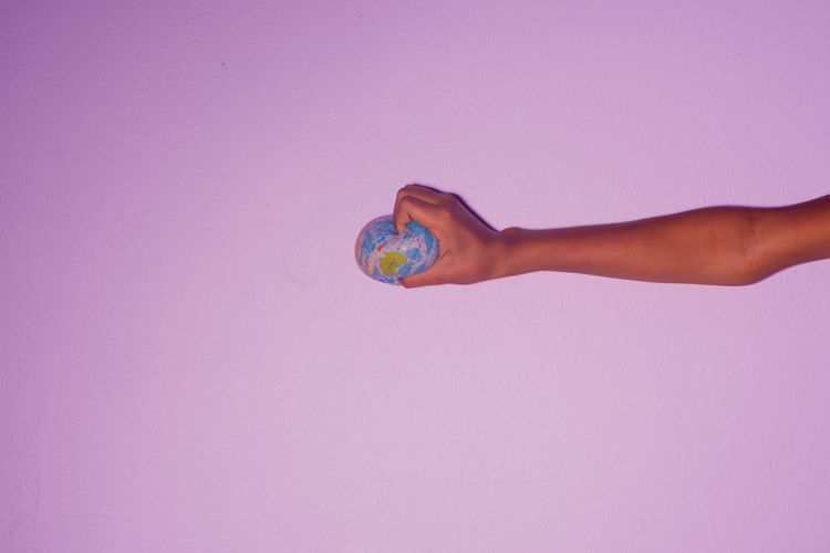 Flat earth Copy Space One Person Human Body Part Studio Shot Indoors  Body Part Finger Human Limb Sphere Fragility Holding Hand Colored Background Human Hand Ball Vulnerability  Limb Purple