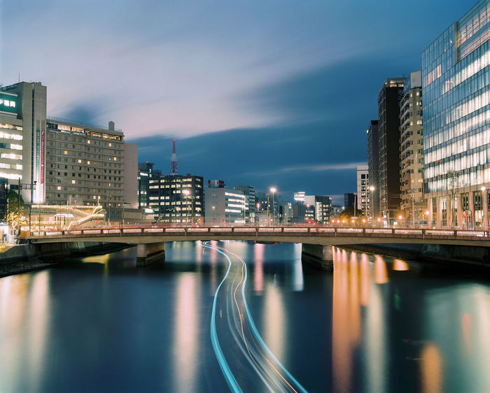 A long-exposure photograph captures the dynamic city of Fukuoka, Japan. Painterly Architecture Building Exterior Built Structure City City Life Cityscape Dynamic Fukuoka Illuminated Light Trail Long Exposure Modern Motion Night No People Outdoors Reflection Sky Skyscraper Transportation Travel Destinations Urban Water Waterfront