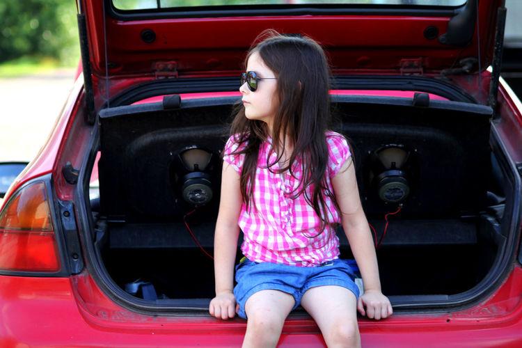 Cute Girl Sitting On Car Trunk