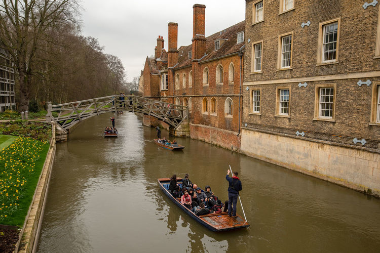 Students of Cambridge University give tourists tours along the River Cam passing under the famous wooden Mathematical Bridge. Cambridge, England. Cambridge Cambridgeshire Quant Pole River Cam University City Boating Boats Mathematical Bridge Punt Pole Punter Punting Punts River River Crossing Transportation Architecture Built Structure Building Exterior Water Nautical Vessel Mode Of Transportation Real People Group Of People Waterfront Canal Men Nature Day Lifestyles Adult City People Outdoors