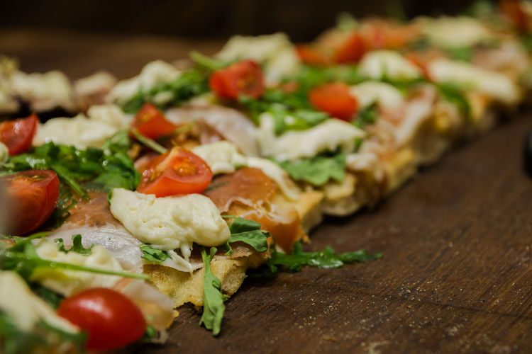 Italian pizza with ham and arugula leaves with cherry tomatoes and mozzarella cheese Food And Drink Food Freshness Vegetable Healthy Eating Selective Focus Still Life Indoors  Ready-to-eat Tomato Close-up Wood - Material Wellbeing Fruit No People Serving Size Table Bread In A Row Pizza Tray Temptation Chopped