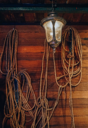 Close-up of rope tied on wooden table against wall