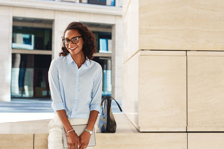 Portrait Of Smiling Businesswoman Wearing Eyeglasses Standing By Wall