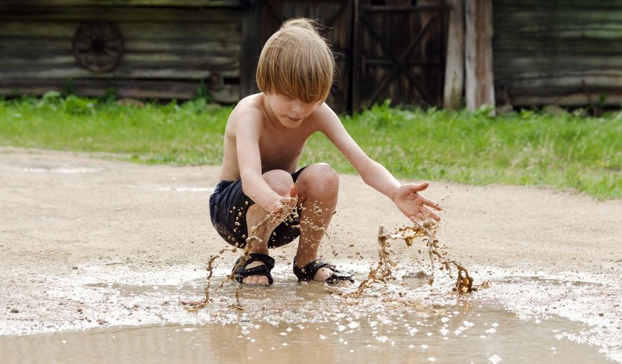Full length of shirtless boy playing with muddy water