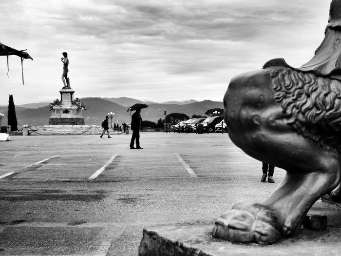 Cropped image of statue by people at piazzale michelangelo in rain