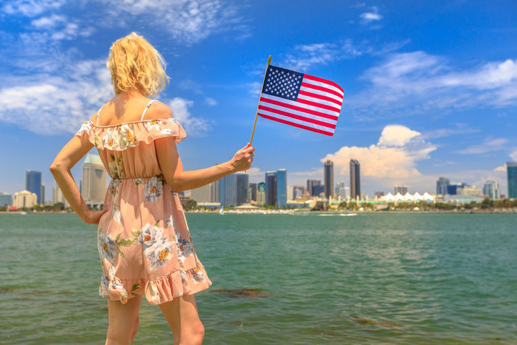 Tourism and travel in California, West Coast, USA. Blonde lady looking San Diego skyline with American flag waving from Coronado Island. Tourist woman in summer holidays. Cityscape in San Diego Bay. United States America American American Flag Woman People Female Girl California San Diego San Diego, California Beach Sea Seascape Skyline Cityscape Shore Nature Vacations Holiday Summer Lifestyles Tourist Coronado Coronado Beach Coronado Island Flag Sky Rear View Water Standing Patriotism Architecture Women One Person Sunlight Real People Day Leisure Activity Outdoors Hairstyle