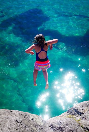 Full length of teenage girl jumping in lake taupo from rock